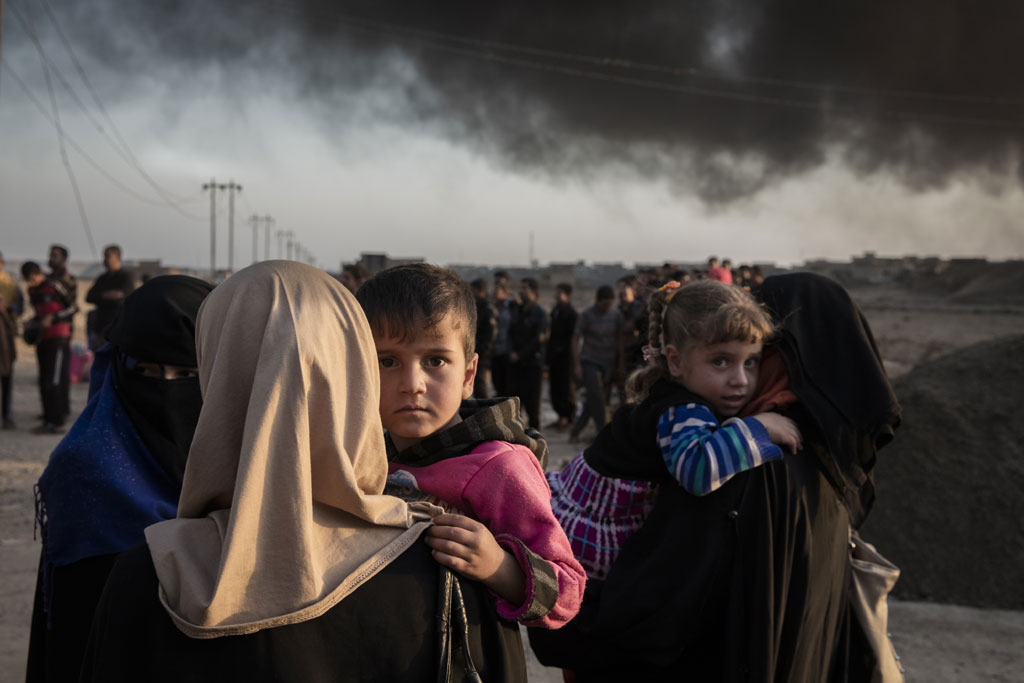 Families displaced by fighting in the village of Shora, 25 kilometres south of Mosul, gather at an army checkpoint on the outskirts of Qayyarah. Photo: UNHCR/Ivor Prickett