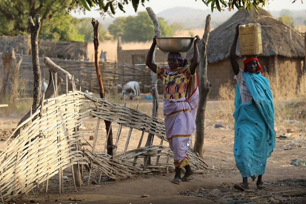 Women in Gordil, Central African Republic (CAR), carry food and water back home as evening descends. Photo: OCHA/Gemma Cortes
