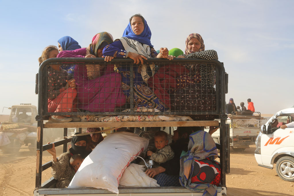 Displaced children and adults in Syria are seen in a vehicle after fleeing from ISIL-controlled areas in rural Raqqa to Ain Issa, the main staging point for displaced families, some 50 kilometres north of Raqqa city. Photo: UNICEF/Delil Soulaiman