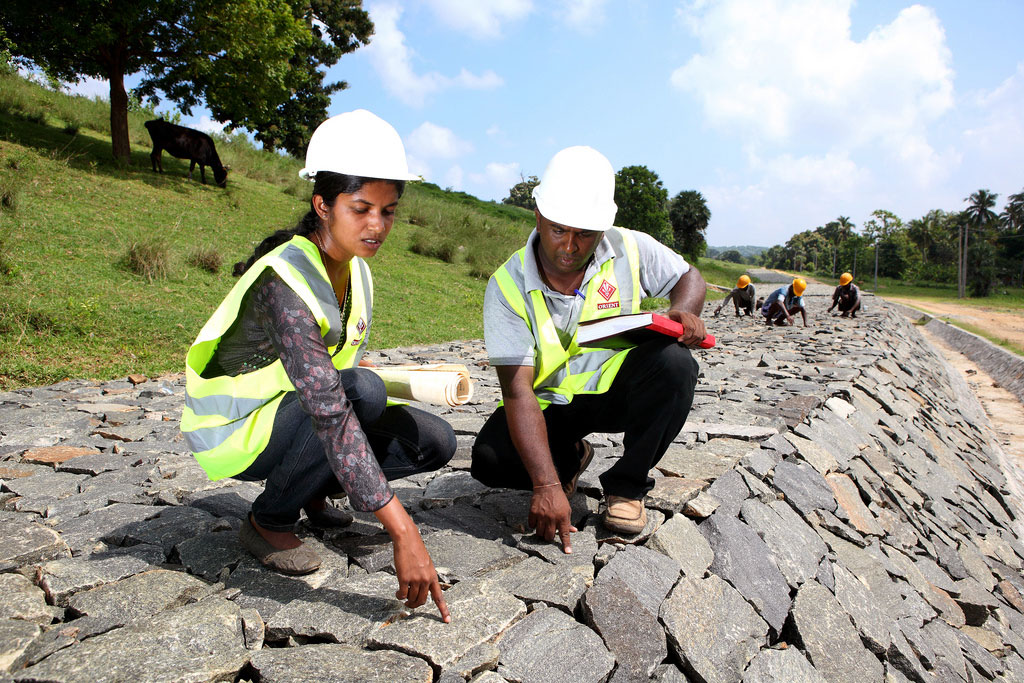 Working alongside her male team member, a woman employee checks the quality of work at a dam under construction in Sri Lanka. Photo: World Bank/Lakshman Nadaraja