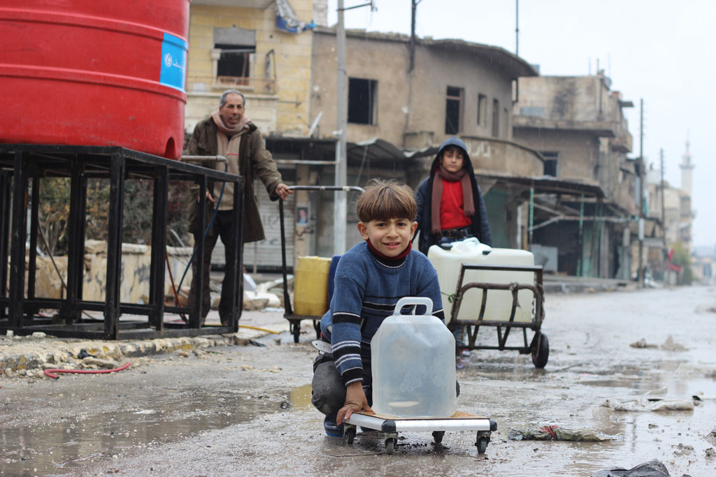 In east Aleppo City, Syria, boys and a man collect water from a UNICEF-supported water point in Shakoor neighbourhood. Photo: UNICEF/Khuder Al-Issa