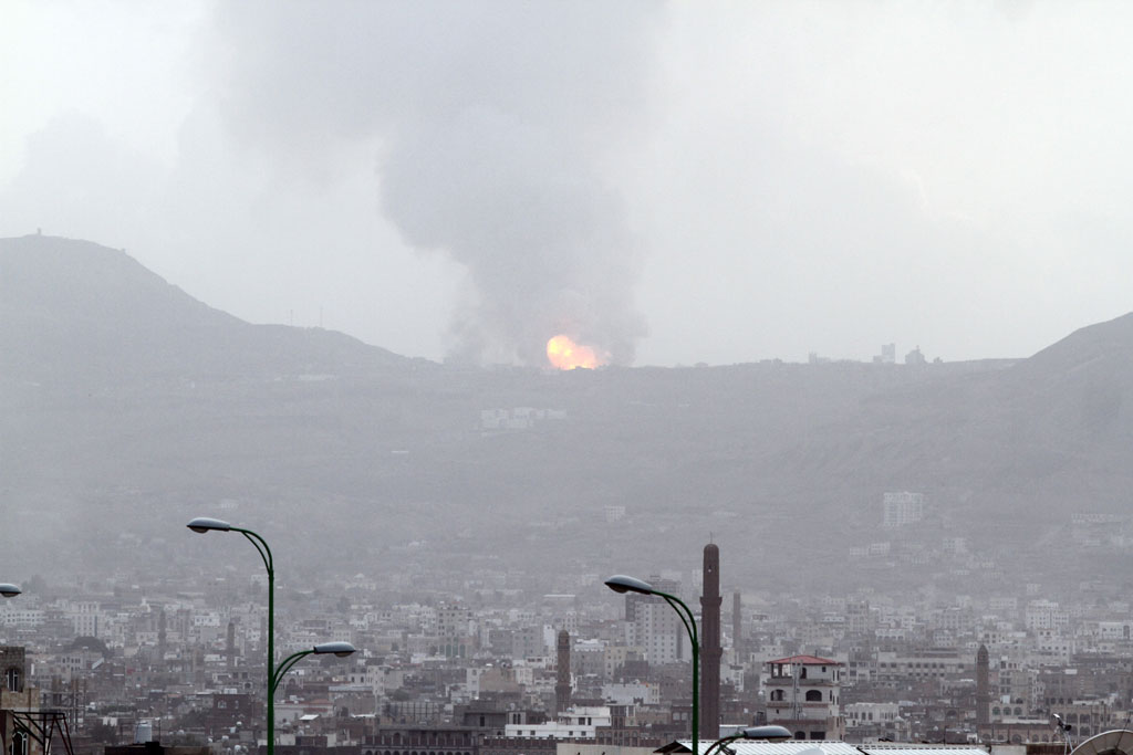 A large ball of fire and plume of smoke – resulting from an air strike that hit a military site on Faj Attan Mountain, Yemen, high above Sana'a, the capital – rises skyward and begins to spread over the city below. Photo: UNICEF/Mohammed Hamoud