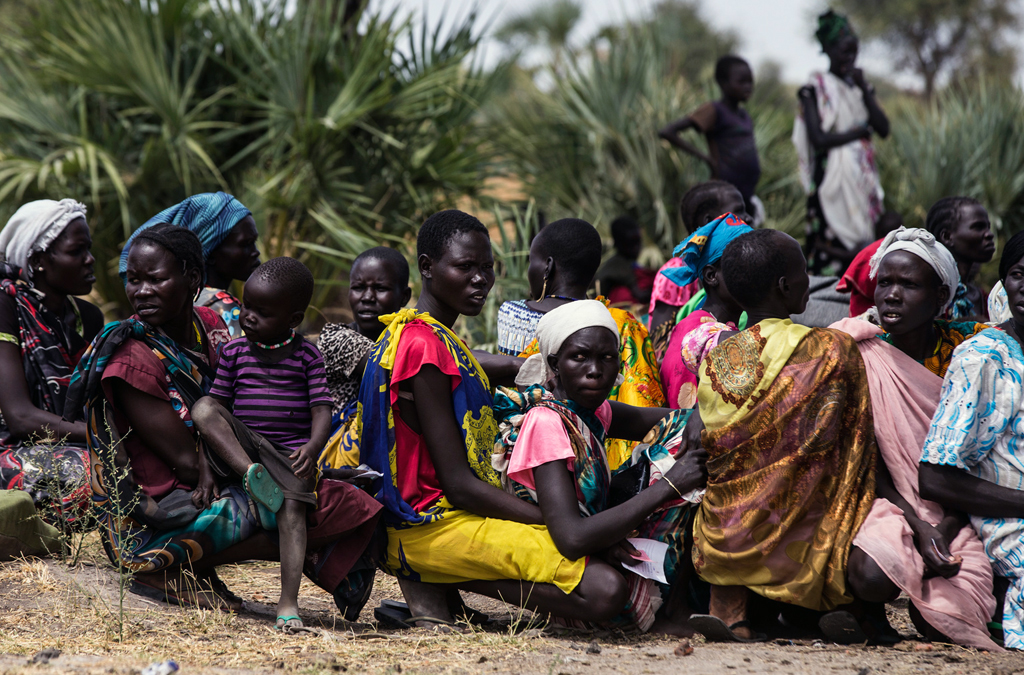 Women wait with their children to be examined and possibly give supplementary food at a mobile clinic run by UNICEF in the village of Rubkuai, Unity State, South Sudan. February 2017. Photo: UNICEF/Modola