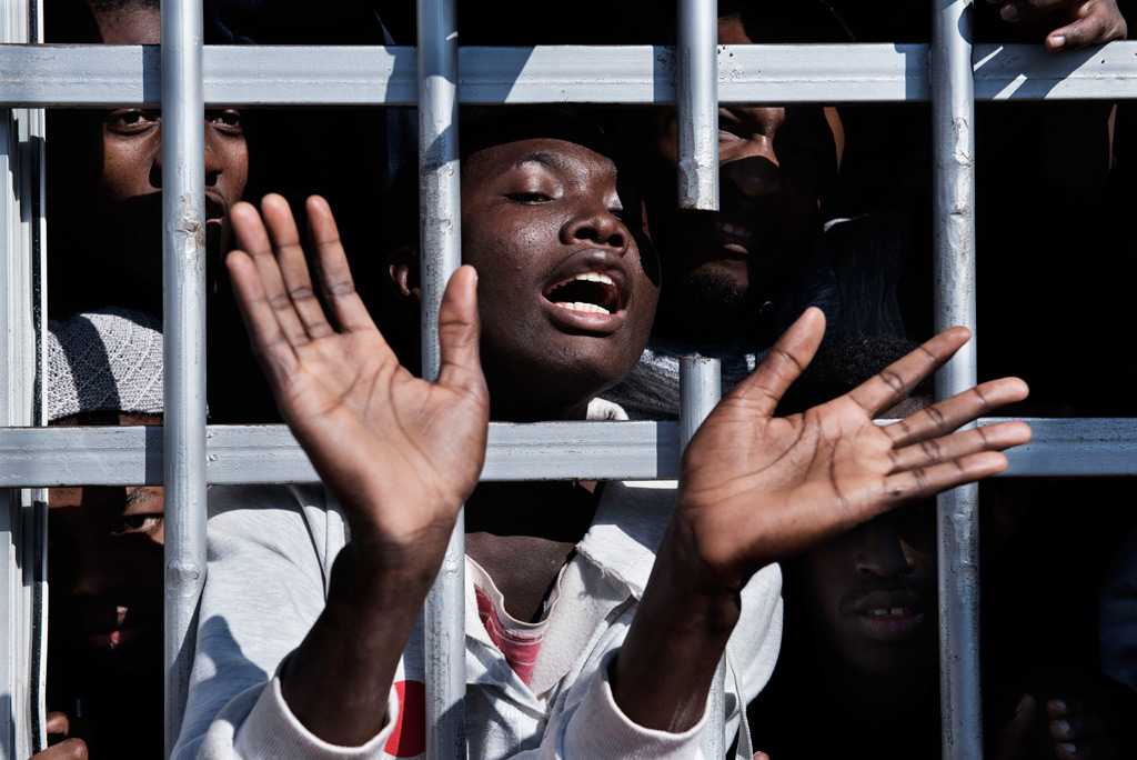 A migrant gestures from behind the bars of a cell at a detention centre in Libya, Tuesday 31 January. Photo: UNICEF/Romenzi