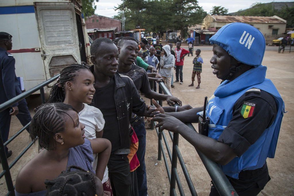 Senegalese peacekeepers from the UN Multidimensional Integrated Stabilization Mission in Mali (MINUSMA) Formed Police Unit (FPU) speak with Malians while they patrol outside Mamadou Konate Stadium during an event to promote peace among the youth. UN Photo/Marco Dormino