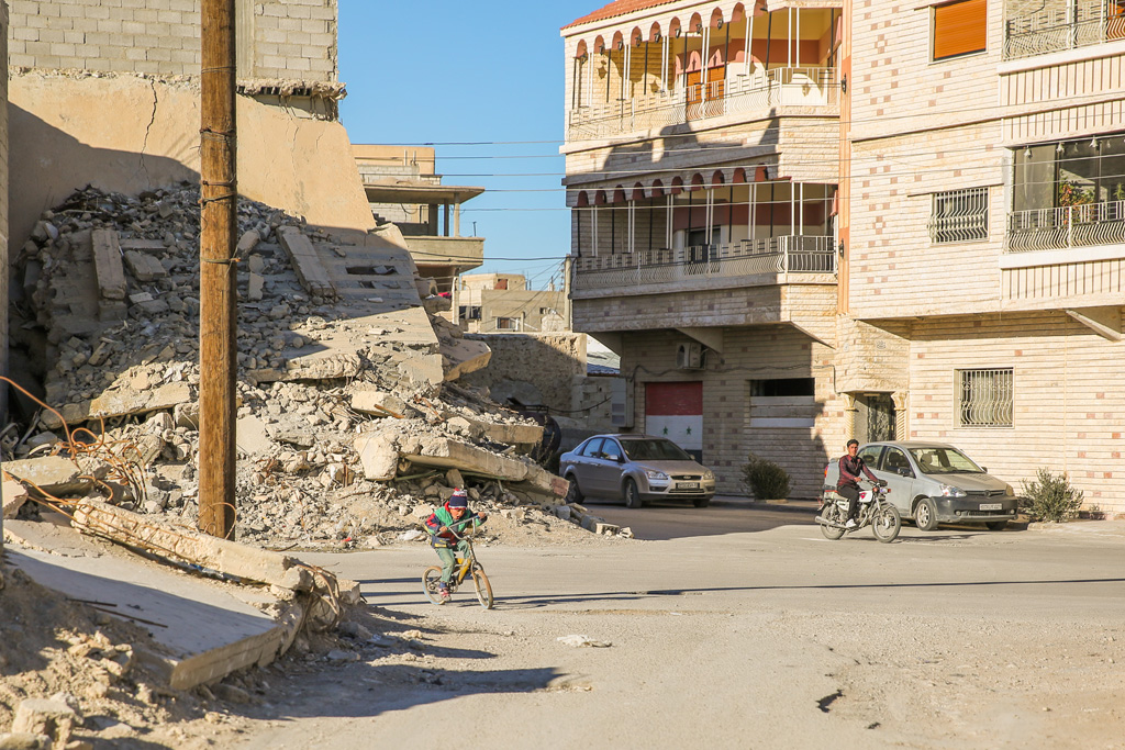 A boy cycles past the rubble of a destroyed house in Qara, where fighting erupted in 2014, dragging the town into the brutal Syrian conflict. Photo: UNHCR/Qusai Alazroni
