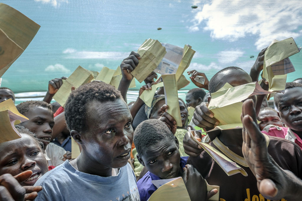 Waving their forms, recently arrived South Sudanese refugees demand to be registered at Imvepi reception centre in Arua district in Northern Uganda. Photo: UNHCR/Jiro Ose