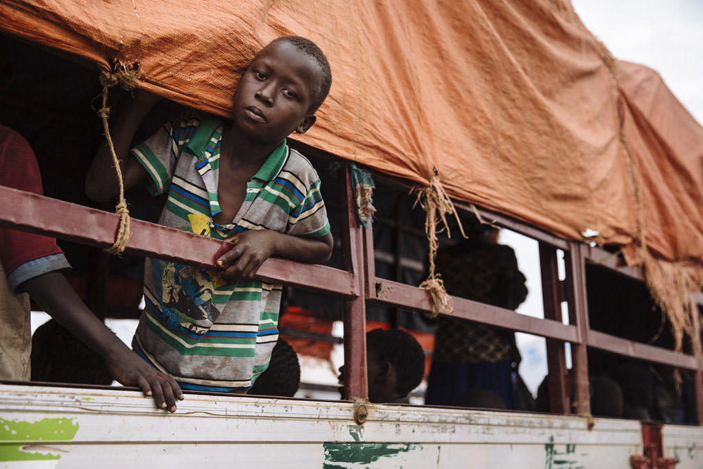 A young South Sudanese refugee looks out of a truck before being transported to the Imvepi settlement at the Imvepi Reception Centre, Arua District, in northern Uganda. Photo: UNHCR/David Azia