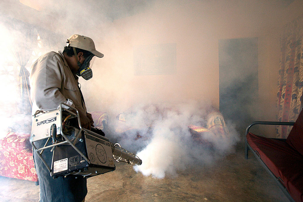 An exterminator fumigates a house in Panama City, Panama, to control mosquito population. PAHO/WHO Photo