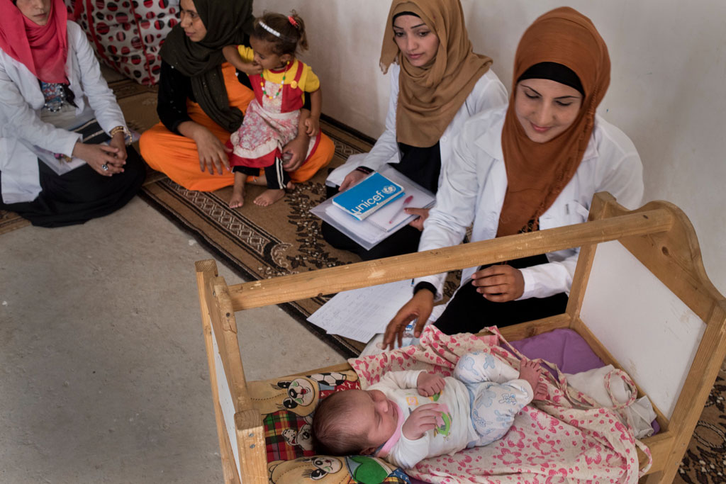 Health workers supported by UNICEF and the Directorate of Health visit a newborn and her mother in their shelter in Debaga displacement camp in Erbil Governorate, Kurdistan Region of Iraq