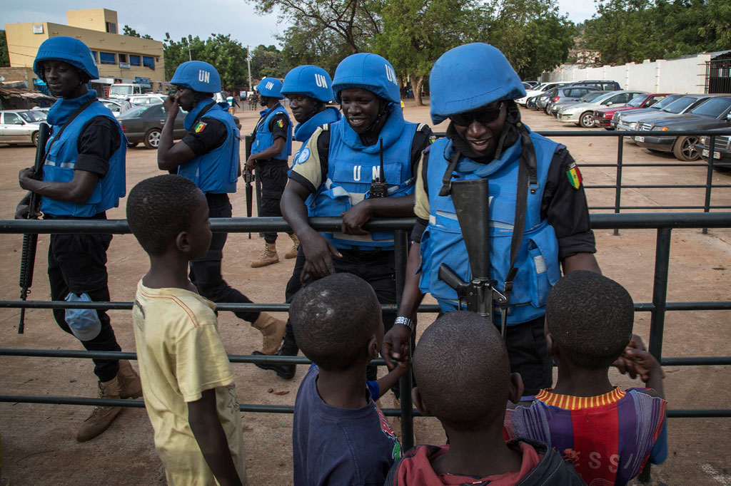 Peacekeepers with the United Nations Multidimensional Integrated Stabilization Mission in Mali (MINUSMA) are greeted by children. Photo: MINUSMA/Marco Dormino