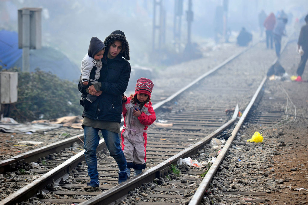 Walking along the train tracks connecting Greece and the former Yugoslav Republic of Macedonia, a woman carries a young boy as a young girl holds on to the back of her jacket. Photo: UNICEF/UN012803/Georgiev