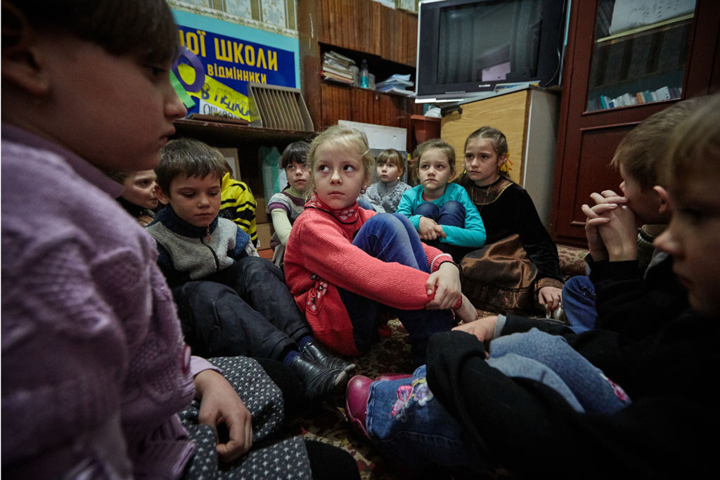 On 13 February 2017, first-grade students in eastern Ukraine, including 6-year-old Sasha (in red sweater), participate in a drill to practice their response to a shelling. Photo: © UNICEF/UN053119/Zmey