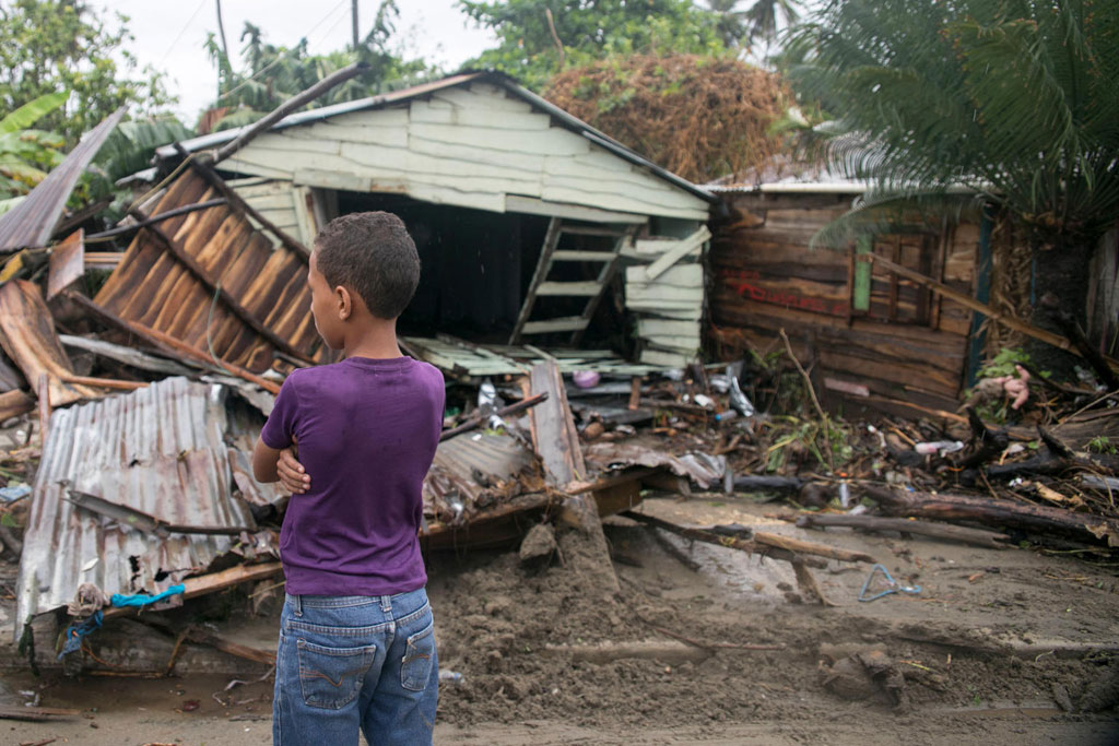 """On 7 September 2017 in Boba, Nagua, a boy, 7, stands in front of debris as Hurricane Irma moves off from the northern coast of the Dominican Republic.  More than 10.5 million children live in the countries that are likely to be exposed to the damage from Hurricane Irma, UNICEF warned today. Based on the storm's current trajectory, children in the islands of the Eastern Caribbean, Dominican Republic, Haiti and Cuba are at risk, including over 3 million under 5 years old. UNICEF is concerned that hundreds of thousands of children could suffer the worst effects of the storm, with those living in coastal zones at highest risk.   """"Strong winds and torrential rains have already barreled through some of the smallest and most exposed islands in the eastern Caribbean, including Anguila and Barbuda,"""" said Patrick Knight, Head of Communication for UNICEF in the Eastern Caribbean, speaking from Barbados. """"As the extent of the damage becomes clear we are seeing severe levels of destruction. Our priority is to reach all those children and families in the affected communities as soon as possible.""""   Hurricane Irma, a Category 5 storm, travelled across various islands of the Eastern Caribbean on Wednesday, leaving a trail of destruction in its path, especially in Anguila, the British Virgin Islands, Barbuda and Turks and Caicos Islands.   Early estimates suggest that 74,000 people, including 20,000 children, have been affected in these islands.   According to local authorities, communication networks in many of the affected areas have been affected either totally or partially. Infrastructure, including roads, bridges, hospitals and schools have also suffered varying degrees of damage. In Barbuda, 90 per cent of the infrastructure has been destroyed, and it is anticipated that this will include up to 132 schools.   UNICEF's immediate concern is providing drinking water and sanitation to affected communities, as well providing child protection services for both children and ado"""