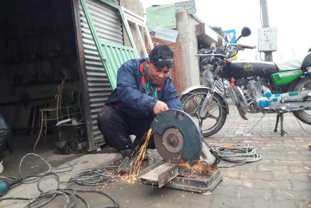 Hassan Hosseini working in a metal workshop that he partially owns, due to assistance from UN migration agency (IOM) offices in Greece and Afghanistan. Photo: IOM