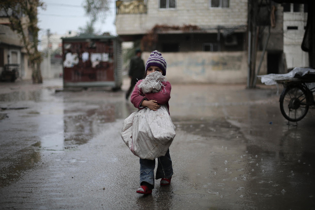 A child carries a bag of firewood she bought for her family in besieged east Ghouta, Syria. Photo: UNICEF/Al Shami